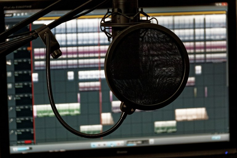 Pop filter (a mesh disc with a thin bezel) suspended in front of a microphone with a computer screen in the background.
